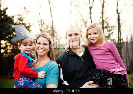 Portrait of happy family in backyard during St. Patrick's Day - Stock Photo