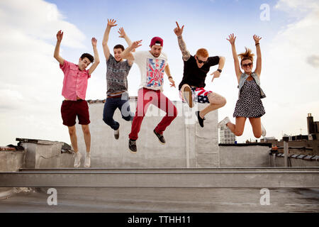Excited friends jumping at building terrace - Stock Photo