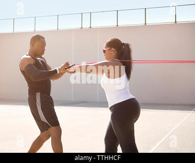 Coach helping sportswoman in pulling ropes on sunny day - Stock Photo