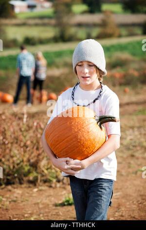 Teenage boy holding pumpkin while walking in farm - Stock Photo