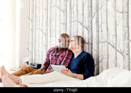 Gay men kissing while resting on bed - Stock Photo