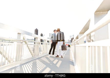 Boyfriends kissing while standing on footbridge during sunny day - Stock Photo