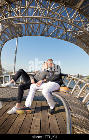 Boyfriends kissing while sitting on metal seat - Stock Photo