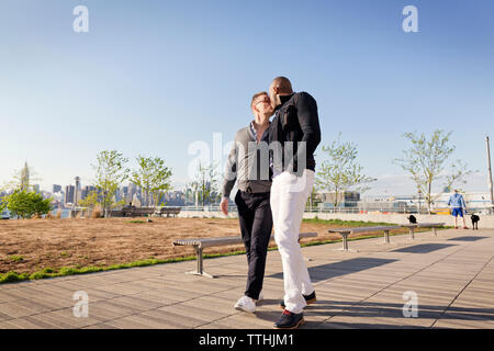 Gay men kissing while walking on footpath in park against clear sky - Stock Photo
