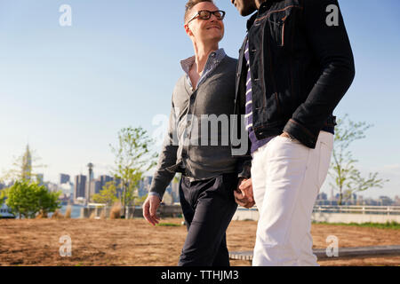 Smiling man looking at boyfriend while walking in park - Stock Photo