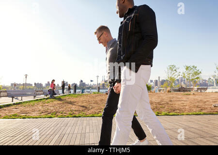 Side view of boyfriends walking on footpath in park - Stock Photo