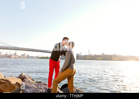 Man kissing boyfriend while standing on rocks by East River on sunny day - Stock Photo