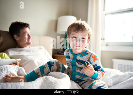 Happy boy enjoying with father while brother using tablet computer on bed at home - Stock Photo