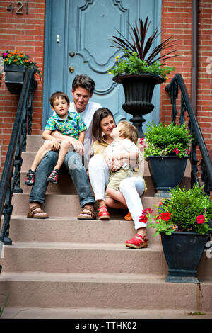 Happy family sitting on steps outside house - Stock Photo
