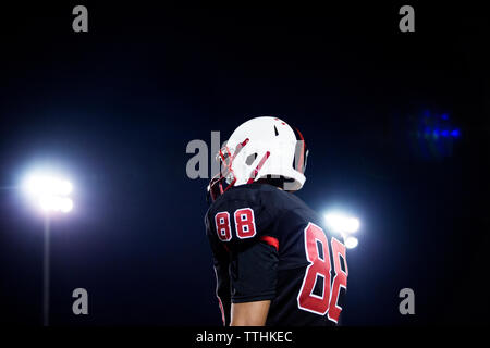 Low angle view of teenage American football players standing against sky at night - Stock Photo