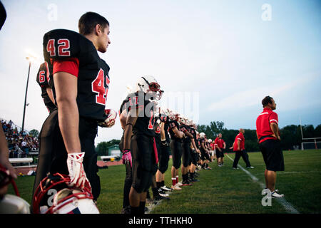 American football team standing on grassy field against sky - Stock Photo