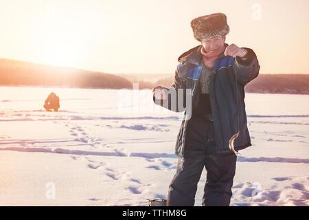Portrait of senior man holding fish while standing on frozen lake - Stock Photo