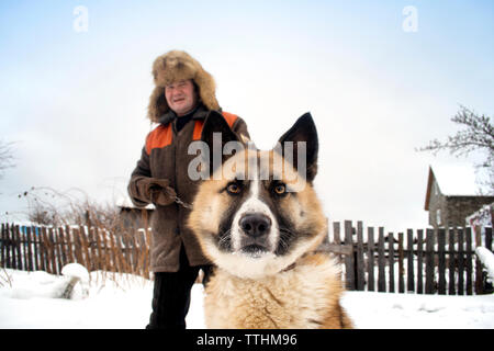Portrait of man and dog on snow covered field - Stock Photo