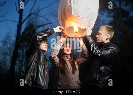 Low angle view of friends holding illuminated paper lantern - Stock Photo