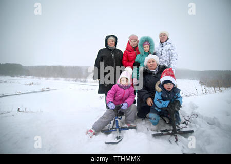 Happy family on snow covered field against sky - Stock Photo