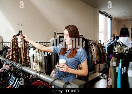 Woman checking clothes in store - Stock Photo