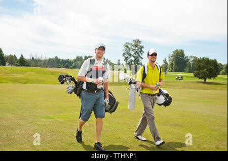 Male friends walking on golf course - Stock Photo