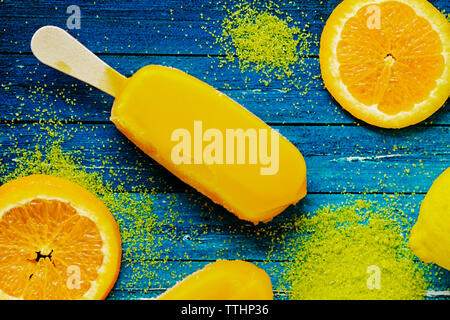 Overhead view of popsicle by orange slices and powder on table - Stock Photo