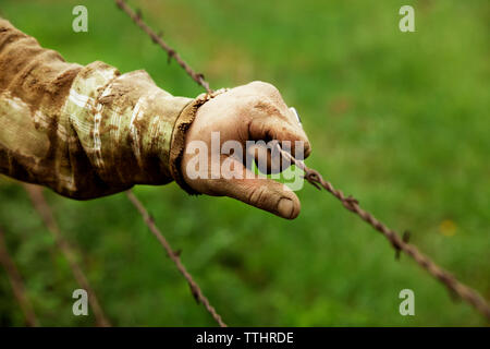 Cropped image of farmer holding barbed wire fence - Stock Photo