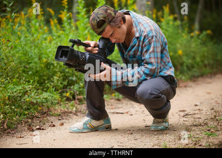Man using video camera while crouching on dirt road - Stock Photo
