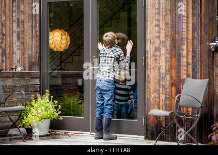 Cheerful boy looking at brother through glass door - Stock Photo