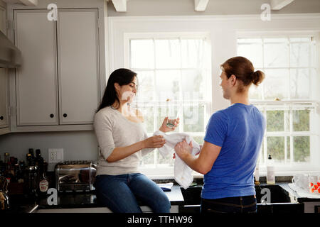 Couple washing dishes in kitchen at home - Stock Photo