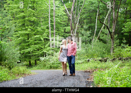 Couple walking on gravel road by field - Stock Photo