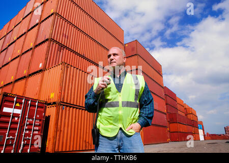 Low angle view of worker standing against cargo containers - Stock Photo