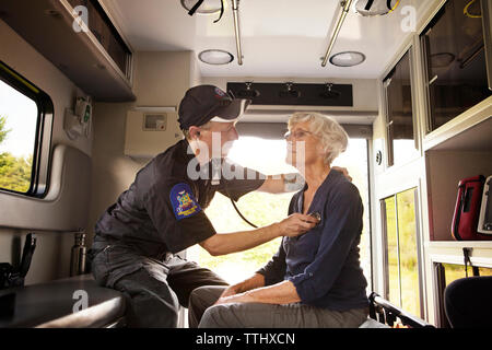 Paramedics examining patient with stethoscope while sitting in ambulance - Stock Photo