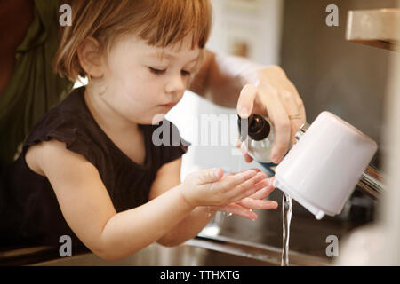 Cropped image of mother assisting daughter in washing hands at home - Stock Photo