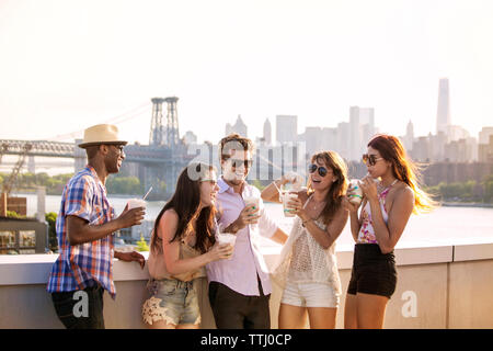 Happy friends drinking iced coffee while standing on building terrace against Williamsburg Bridge - Stock Photo