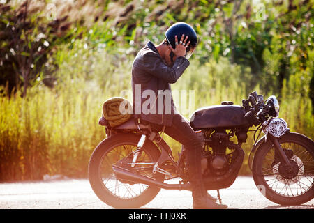 Side view of man sitting on motorcycle - Stock Photo