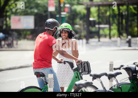 Man looking at woman fastening cycling helmet while standing on road - Stock Photo