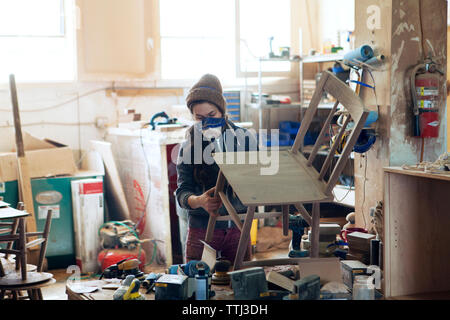 Female carpenter examining wooden chair in workshop - Stock Photo