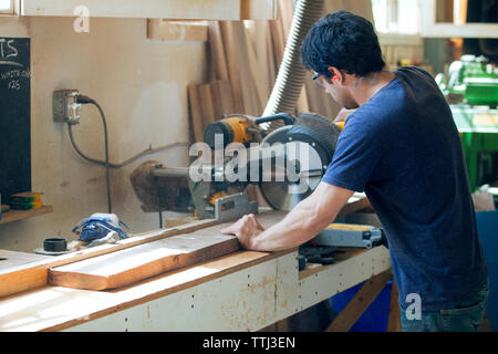 Side view of male carpenter cutting wooden plank with electric saw - Stock Photo