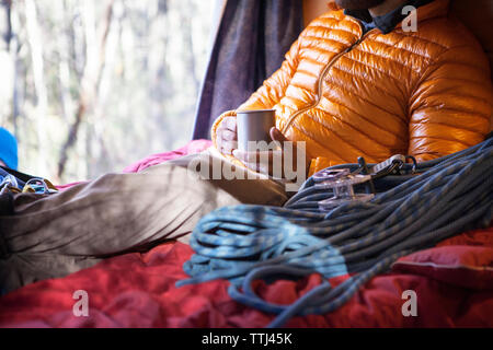 Midsection of man holding mug while sitting on bed in camper van - Stock Photo