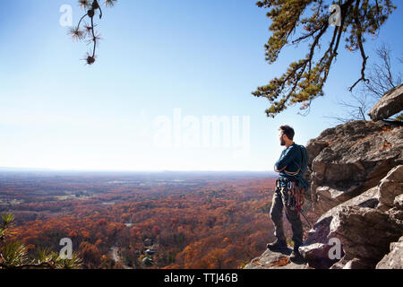 Man standing on rocks against sky - Stock Photo