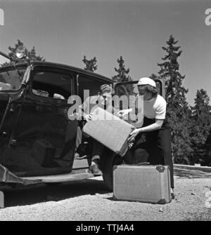 Couple in the 1950s. A young couple are packing  their  luggage for a car vacation. Sweden 1952 Kristoffersson BF76-10 - Stock Photo