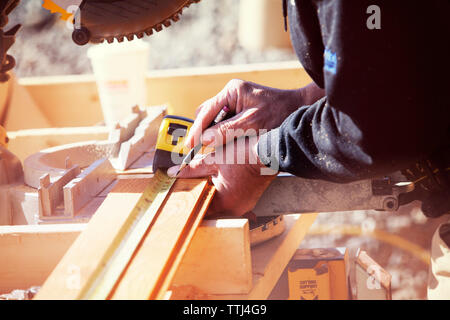 Midsection of worker measuring wooden planks at construction site - Stock Photo