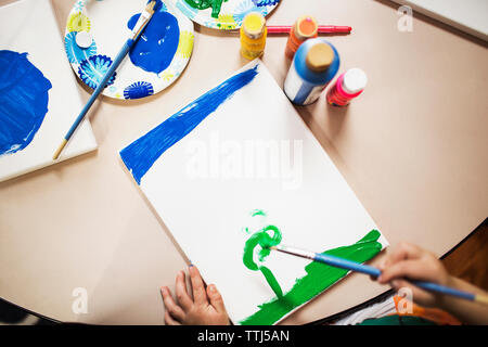 High angle view of boy painting at table - Stock Photo