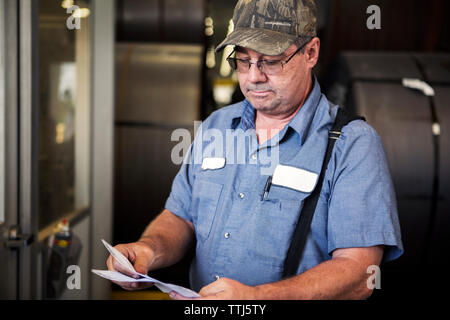 Serious worker examining documents while standing in metal industry - Stock Photo