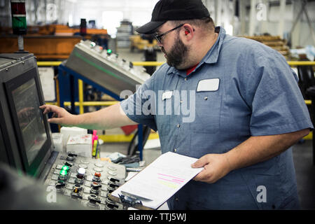 Overweight manual worker operating machinery at control panel in metal industry - Stock Photo
