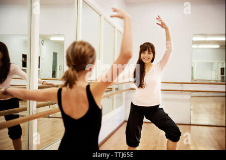Girl dancing with teacher in dance studio - Stock Photo