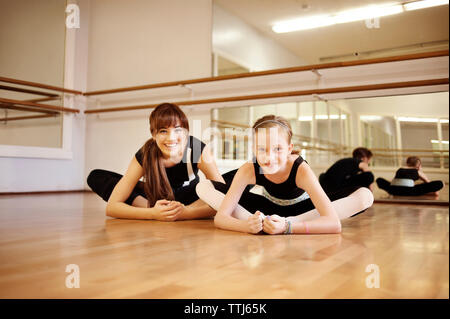 Portrait of teacher and student practicing Cobbler pose in dance studio - Stock Photo