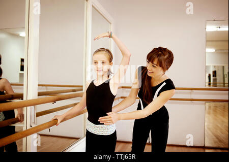 Happy teacher guiding student in dance studio - Stock Photo