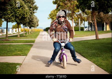 Portrait of woman riding bicycle at park - Stock Photo