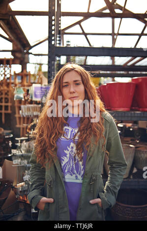 Portrait of confident woman standing in plant nursery - Stock Photo