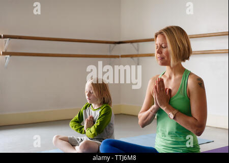 Boy exercising with trainer in yoga class - Stock Photo