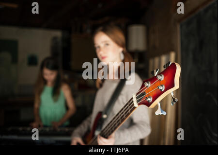 Girl playing guitar with friend in background - Stock Photo