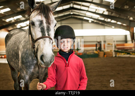 Portrait of boy with horse standing in stable - Stock Photo